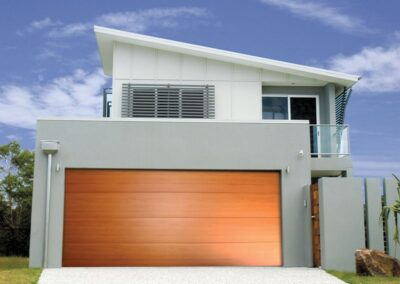 A smooth sleek garage door Flatline profile in Western Red Cedar colour